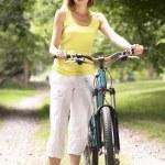 Woman riding bike in countryside — Stock Photo