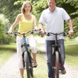 Couple riding bikes in countryside — Stock Photo