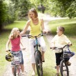 Foto Stock: Mother and children riding bikes in countryside