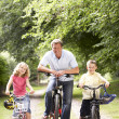 Father and children riding bikes in countryside — Stockfoto