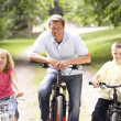 Stock Photo: Father and children riding bikes in countryside