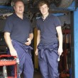 Mechanic and apprentice working on car - Foto Stock