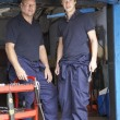 Mechanic and apprentice working on car - Stock fotografie