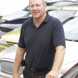 Stock Photo: Car salesmstanding on lot