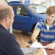 Stock Photo: Young mfilling in paperwork in car showroom