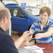 Young man filling in paperwork in car showroom — Stock Photo