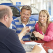 Couple filling in paperwork in car showroom — Stock Photo