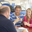 Couple filling in paperwork in car showroom — Stok fotoğraf