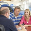 Couple filling in paperwork in car showroom - ストック写真
