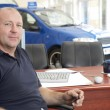 Car salesman sitting in showroom - Stock Photo