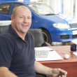 Car salesman sitting in showroom smiling - Stock Photo