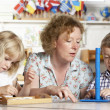 Adult Helping Two Young Children at Montessori/Pre-School — Stock Photo #4815468