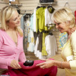 Sales assistant with customer in clothing store — Stock Photo