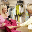 Sales assistant with customer in clothing store — Stok fotoğraf