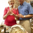 Stock Photo: Middle aged couple shopping for antiques