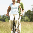 Mature couple riding bike in countryside — Stock Photo