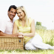 Young couple having picnic in countryside — Stock Photo