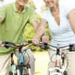 Mature couple riding bikes — Stock Photo
