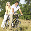 Couple riding tandem in countryside - 图库照片