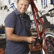 Owner of cycle shop in workshop - Stock Photo