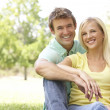 Portrait Of Young Couple Sitting In Park — Stock Photo