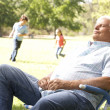 Senior Man Relaxing In Park With Grandchildren In Background — Stock Photo