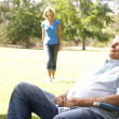 Senior Man Relaxing In Park With Wife In Background - Stock Photo