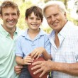 Foto de Stock  : Grandfather With Father And Son Playing AmericFootball Togeth