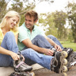 Couple Putting On In Line Skates In Park — Stock Photo #4815833