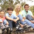 Royalty-Free Stock Photo: Family Putting On In Line Skates In Park