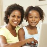 madre e figlia usando il portatile a casa — Foto Stock