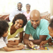 Family Playing Board Game At Home With Grandparents Watching — Stock Photo #4815984
