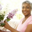 Senior Woman Flower Arranging At Home - Stock Photo