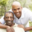 Senior Man Hugging Adult Son - Stock Photo