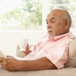 Старший мужчина чтение книги с напитком на дому — Стоковое фото