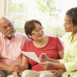 Senior Couple Talking To Financial Advisor At Home - Stock Photo
