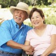 Senior Couple Relaxing In Garden Together - ストック写真