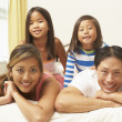 Young Family Relaxing In Bedroom - ストック写真