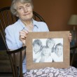 Senior Woman At Home Looking At Photo Of Grandchildren - Stock Photo