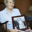 Senior Woman At Home Looking At Old Wedding Photo - Stock Photo