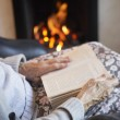 Detail Of Senior Woman Reading Book By Fire At Home — Stock Photo