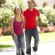 Young Couple Walking Through City Street - Stock Photo