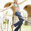 Young Woman Sliding Down Banister Of Building - Foto Stock