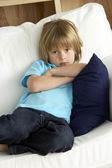 Young Boy Sat on Sofa at Home — Stock Photo