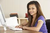 Sorridente ragazza adolescente sul computer a casa — Foto Stock