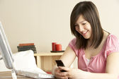 Smiling Teenage Girl using Mobile Phone at Home — Stock Photo