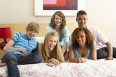 Group Of Five Teenage Friends Hanging Out In Bedroom — Stok fotoğraf