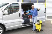 Cleaner standing next to van — Stock Photo