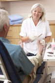 Chirpodist treating client in clinic — Stock Photo