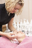 Female masseuse giving client facial — Stock Photo